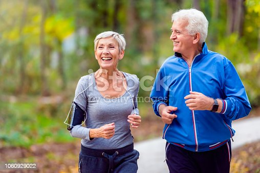istock Smiling senior couple jogging in the park 1060929022