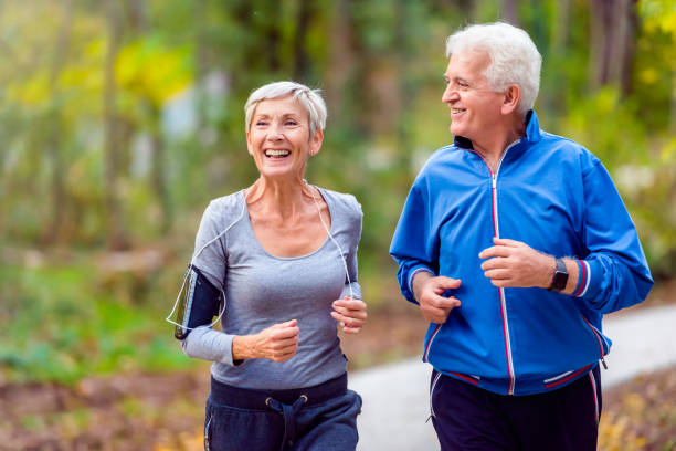 smiling senior couple jogging in the park - idosos imagens e fotografias de stock