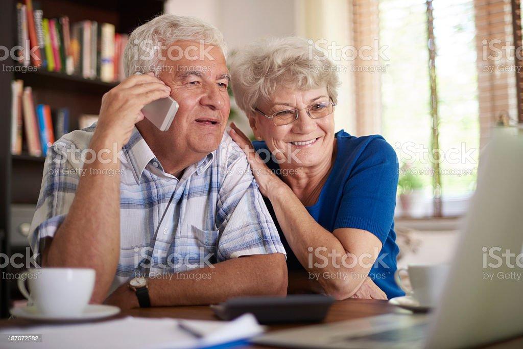Smiling senior couple making  deal via telephone stock photo