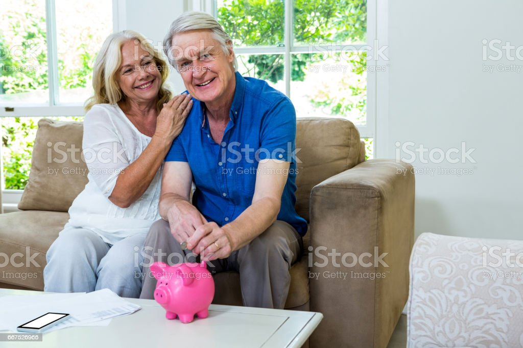 Smiling senior couple putting coin in piggi bank at home stock photo