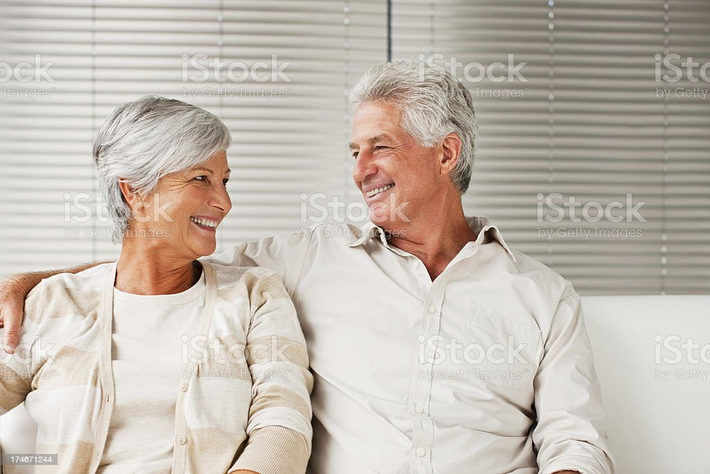 Smiling senior couple sitting on couch royalty-free stock photo