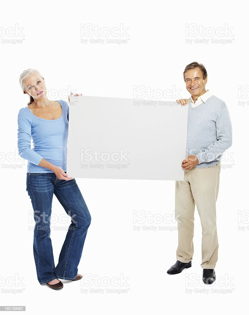 Smiling senior couple standing with an advertising board royalty-free stock photo