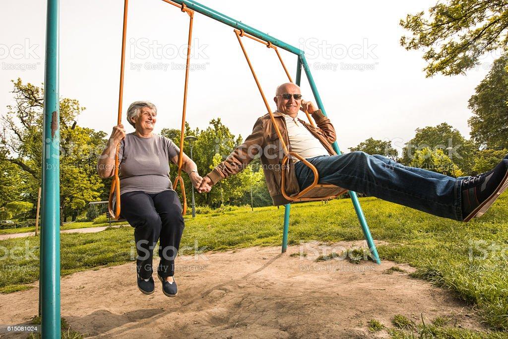 Smiling senior couple swinging together at the playground. stock photo