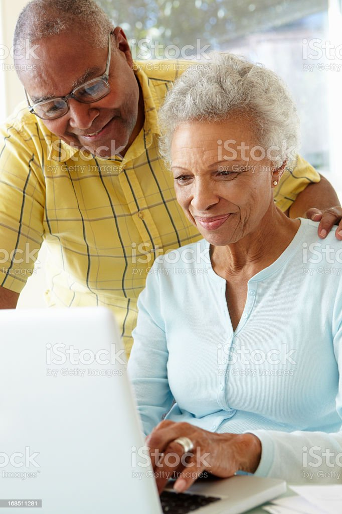 A smiling senior couple using a white laptop at home stock photo
