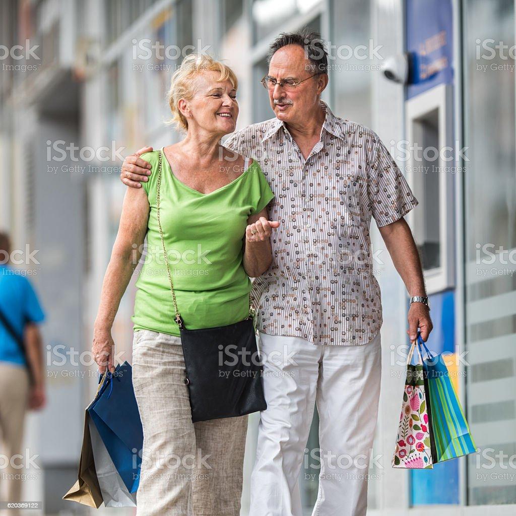 Smiling senior couple walking with shopping bags on the street. zbiór zdjęć royalty-free