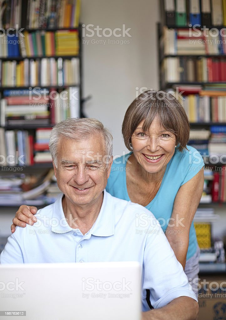 smiling senior couple with laptop surfing the net royalty-free stock photo