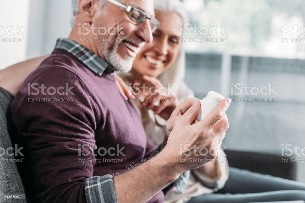 smiling senior couple with pill bottle sitting in sofa at home stock photo