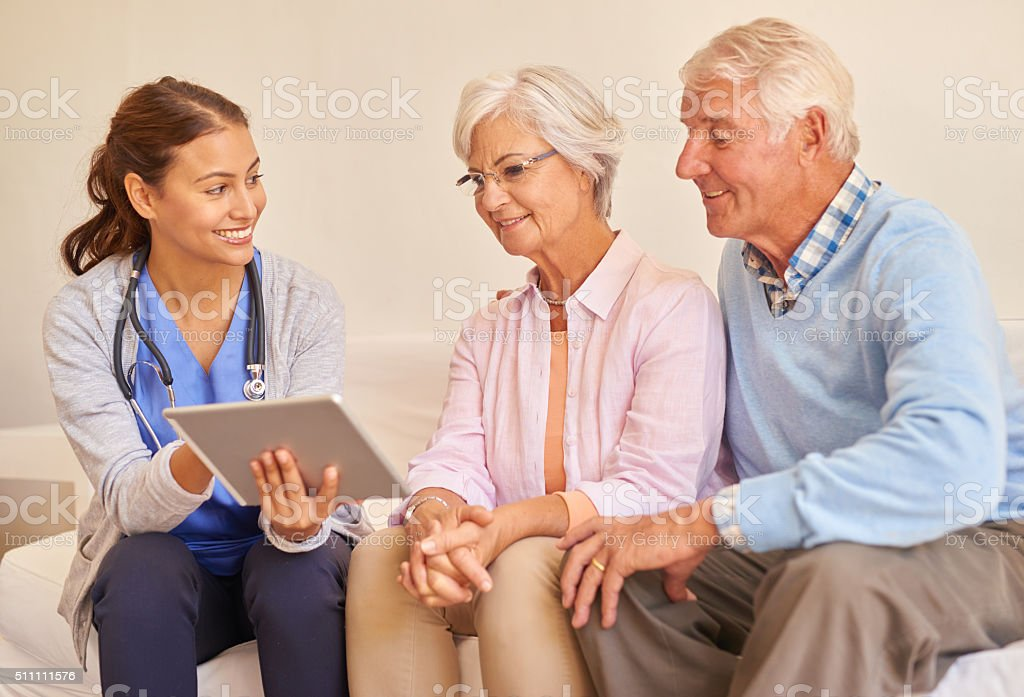 Smiling senior couple with their nurse during an appointment stock photo