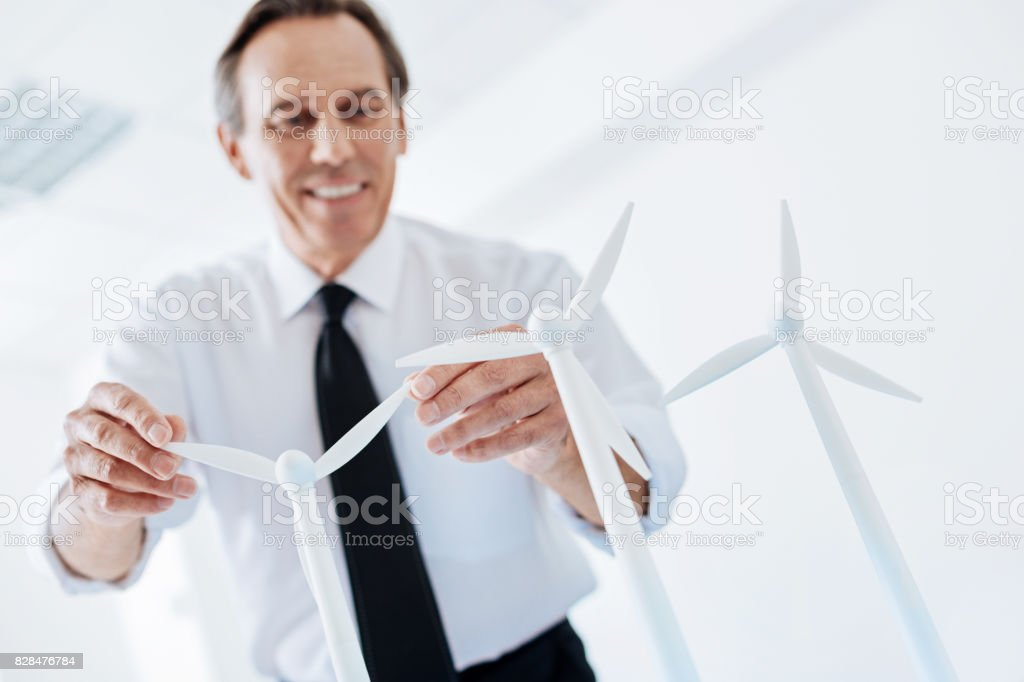 Smiling senior engineer holding two wind turbine sails stock photo