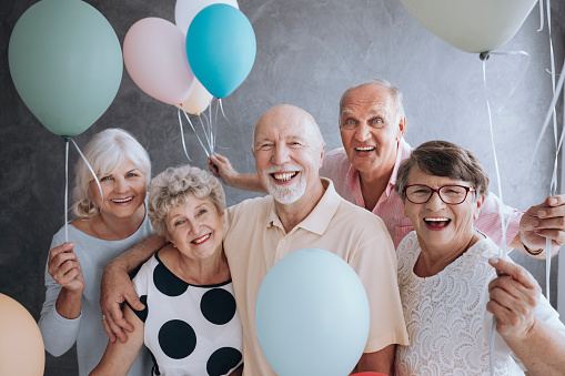 istock Smiling senior friends with colorful balloons enjoying meeting 999638306