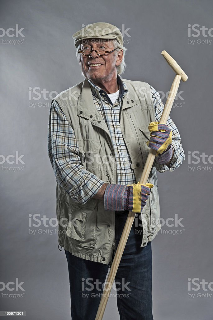 Smiling senior gardener man with hat holding hoe. Wearing glasses. royalty-free stock photo