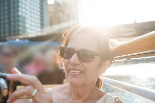 Smiling Senior Hispanic Woman by Chicago Skyline Enjoying Tour
