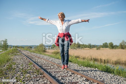 istock smiling senior lady having fun balancing on rails 850858808