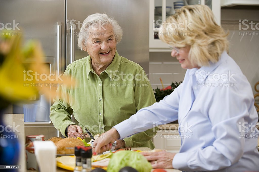 Smiling Senior Lady with a friend in a kitchen stock photo