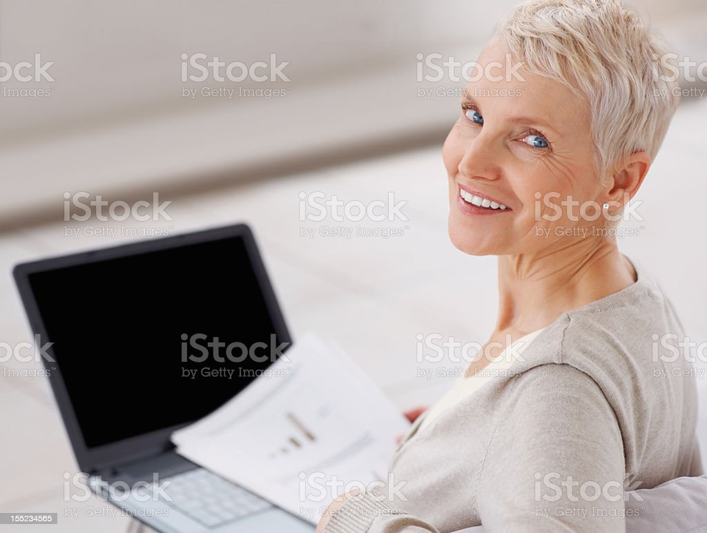 Smiling senior lady with laptop at home royalty-free stock photo