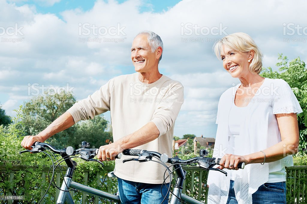 Smiling senior man and woman with their bicycles in countryside royalty-free stock photo