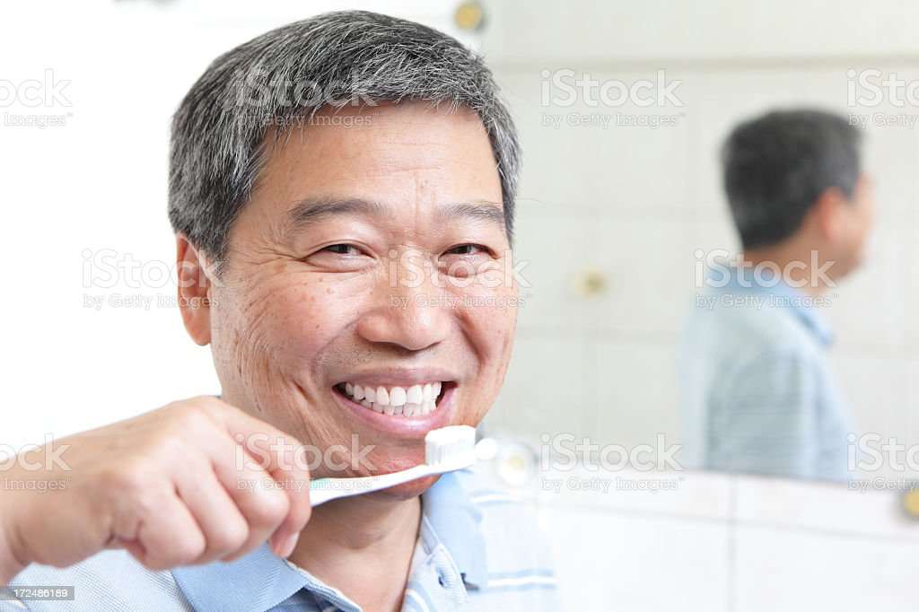 Smiling senior man brushing teeth next to mirror stock photo