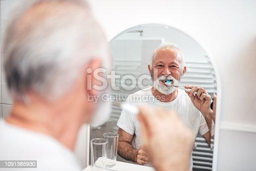 istock Smiling senior man brushing teeth. 1091385930