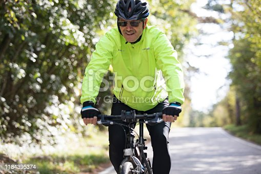 Smiling Senior Man Cycling on Country Road.