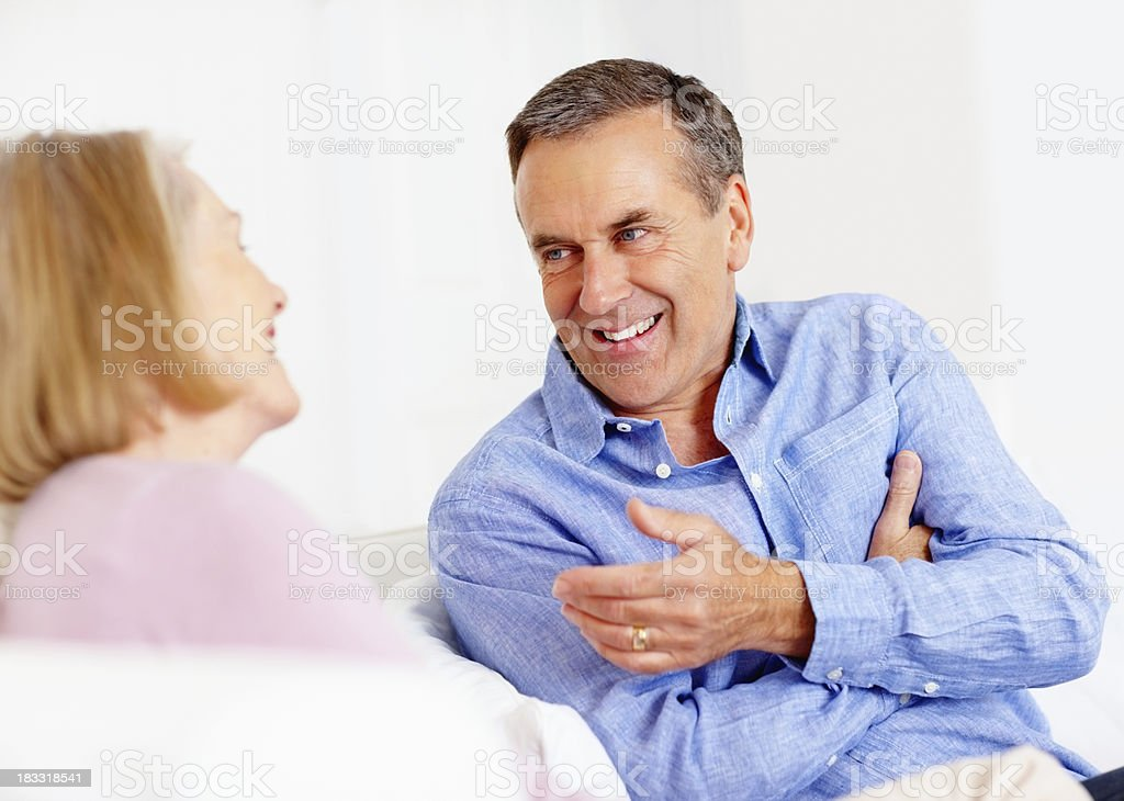 Smiling senior man discussing with his wife at home royalty-free stock photo