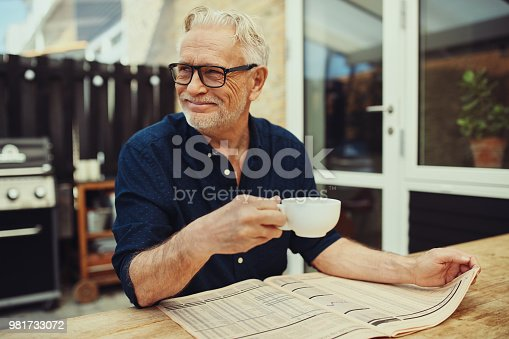116379055 istock photo Smiling senior man drinking coffee and reading a newspaper outside 981733072