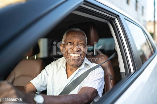 1051147634 istock photo Smiling senior man driving a car and looking at camera 1159586746