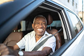 Smiling senior man driving a car and looking at camera