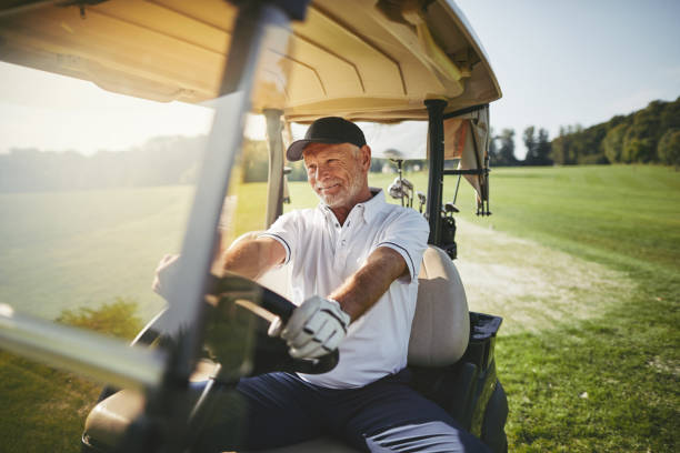 Smiling senior man driving his golf cart on a fairway Smiling senior man driving a golf cart along a fairway while playing a round of golf on a sunny day active seniors stock pictures, royalty-free photos & images