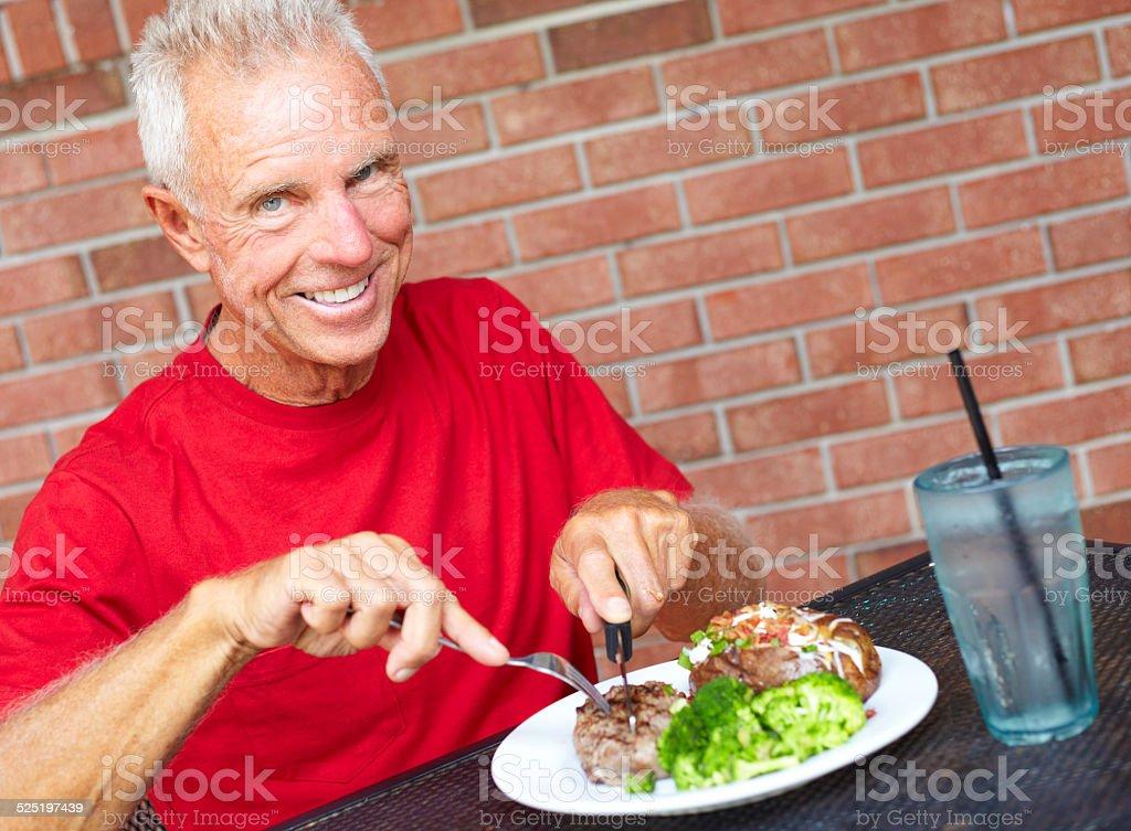 Sorridente homem idoso comer Tira de Carne de vaca no restaurante Mesa - fotografia de stock