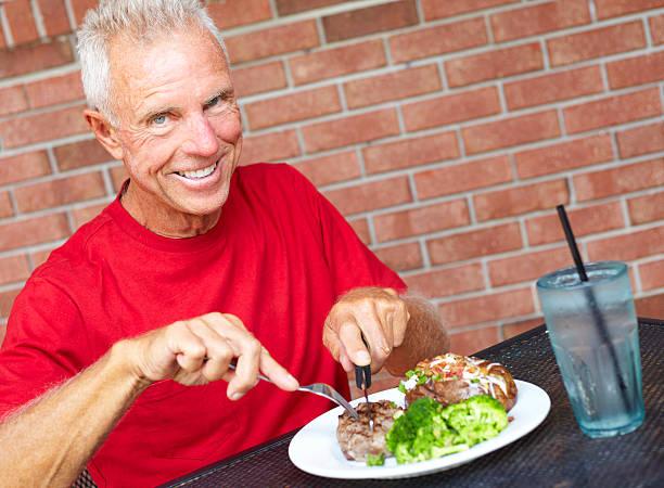 Smiling Senior Man Eating Strip Steak At Restaurant Table stock photo