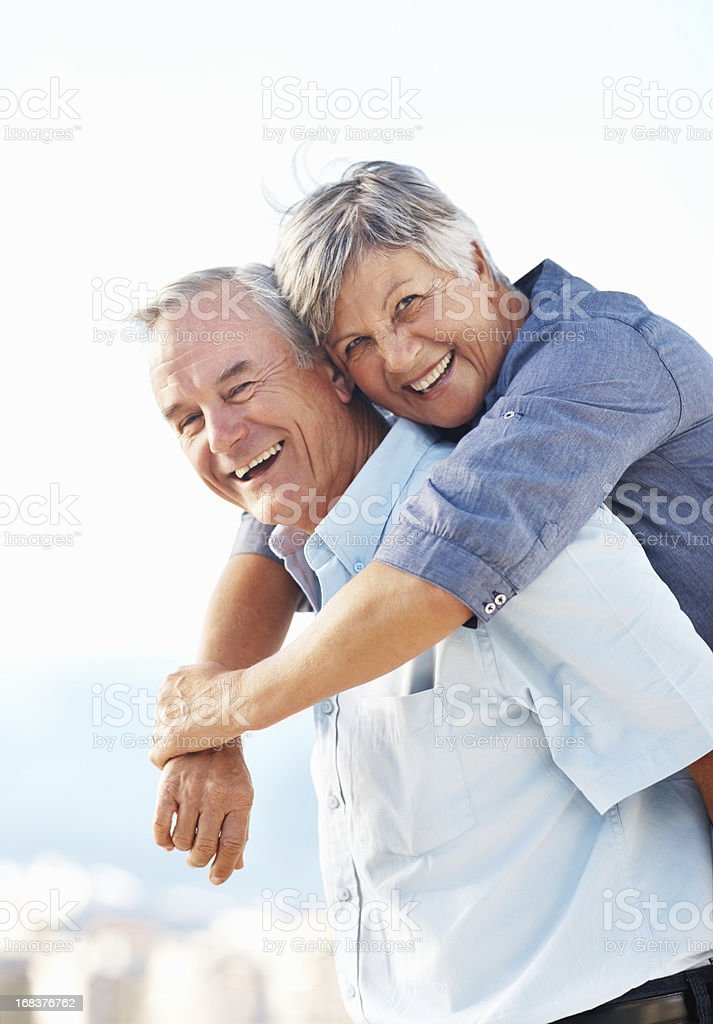 Smiling senior man giving piggeback ride to woman outdoors royalty-free stock photo