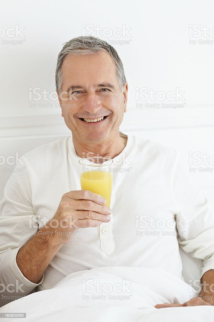 Smiling senior man holding a glass of juice royalty-free stock photo