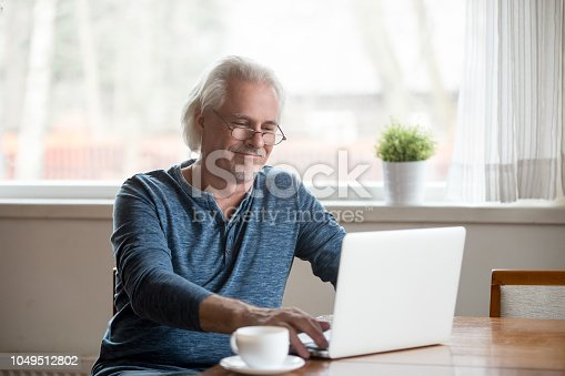 istock Smiling senior man in glasses working on laptop at home 1049512802