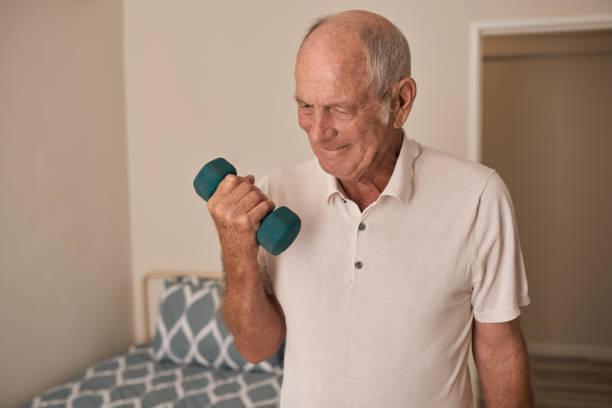 Lächelnder Senior Mann, der Gewichte in seinem Altersheim zimmer – Foto
