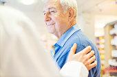 Smiling senior man looking at pharmacist