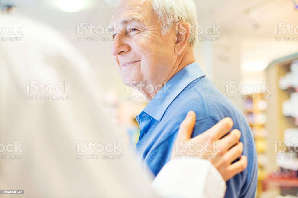 Smiling senior man looking at pharmacist stock photo