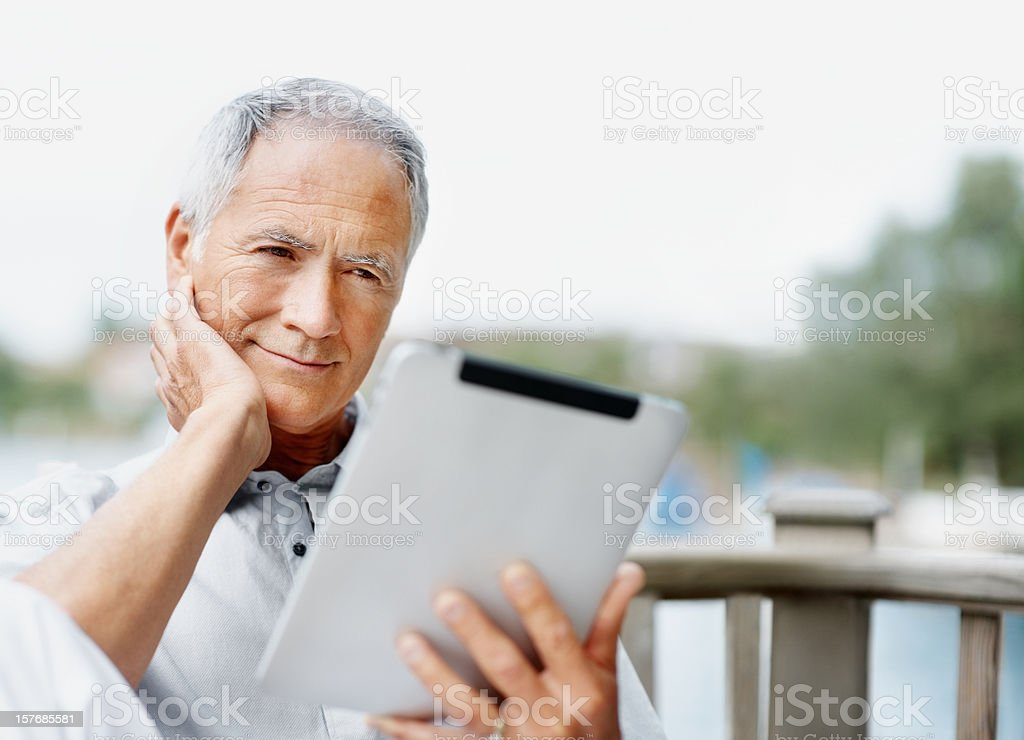 Smiling senior man looking at tablet PC screen stock photo