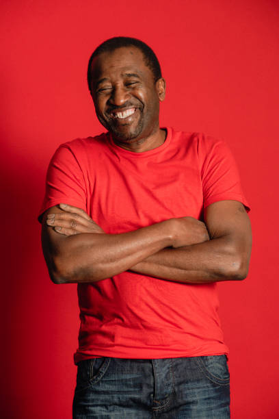 Smiling Senior Man Portrait of a senior African man wearing a red t-shirt, he is standing in front of a red background with arms crossed. red shirt stock pictures, royalty-free photos & images