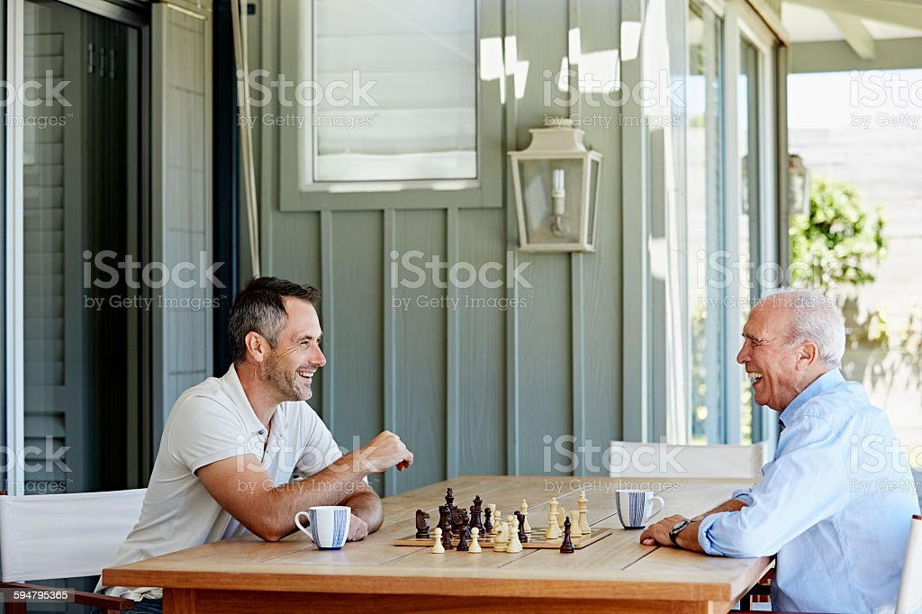 Smiling senior man playing chess with son Side view of smiling senior man playing chess with son on patio 2015 Stock Photo