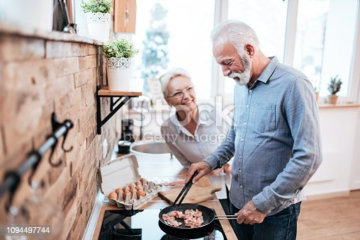 Smiling senior man preparing food for him and his wife in cozy kitchen.