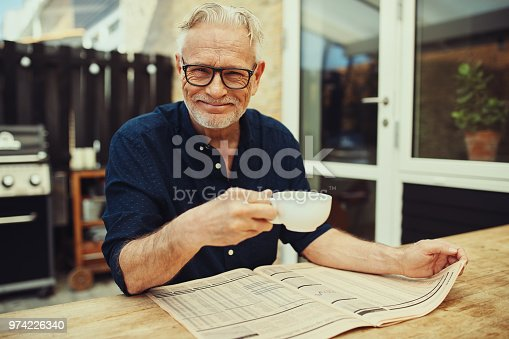 116379055 istock photo Smiling senior man reading a newspaper outside and drinking coffee 974226340