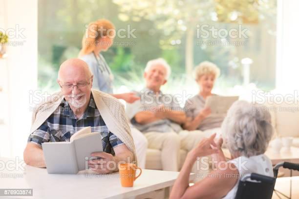 Smiling senior man reading book Senior man reading book and smiling to friend while sitting together at table in nursing house Adult Stock Photo