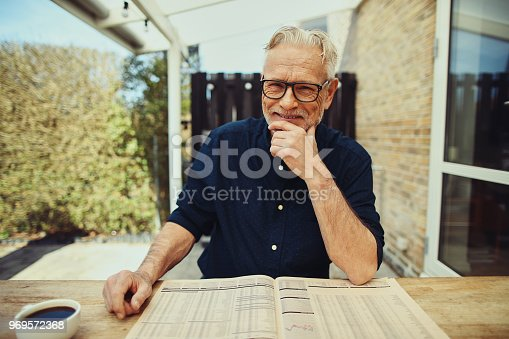 116379055 istock photo Smiling senior man reading the newspaper at his patio table 969572368