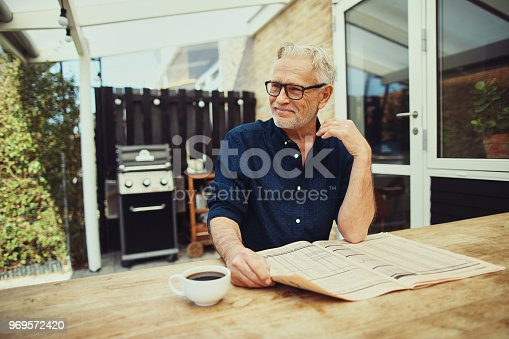 116379055 istock photo Smiling senior man relaxing on his patio reading the newspaper 969572420