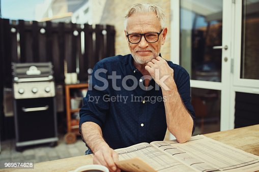 116379055 istock photo Smiling senior man relaxing on his patio with a newspaper 969574628