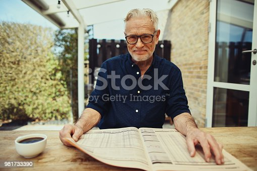 116379055 istock photo Smiling senior man relaxing outside with a coffee and newspaper 981733390