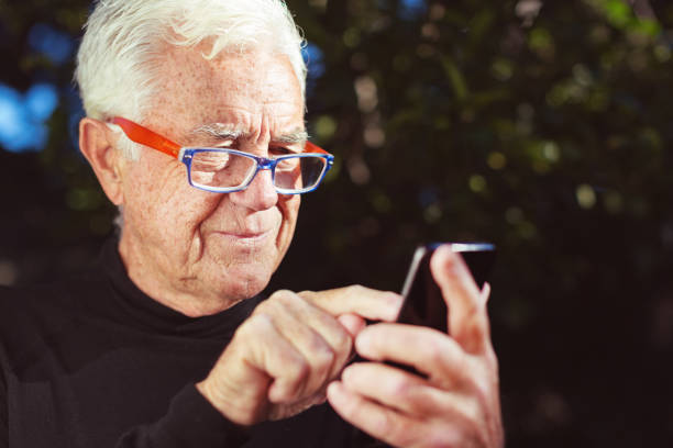 Smiling senior man sending text message on smart phone stock photo