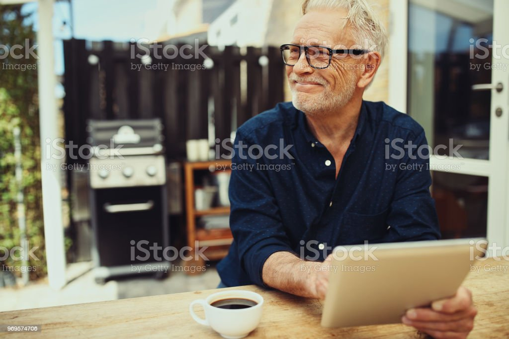 Smiling Senior Man Sitting Outside With A Coffee And Tablet Stock Photo Download Image Now Istock