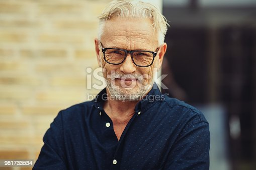 istock Smiling senior man standing in front of his home 981733534