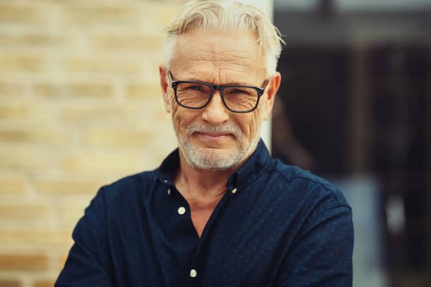 lächelnde senior mann stand vor seinem haus - senior mann porträts stock-fotos und bilder